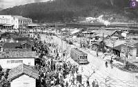 被爆から半年の広島駅前の闇市。1946年1月10日にパターソン米陸軍長官が広島を視察した際の警備上の理由から、駅前広場に面した松原町下の段に移転した。露店に集まる人々と、広島駅舎右手には電停に並ぶ人々の列も見える。電車は、宇品終点付近で被爆し、1945年8月に復旧した650形652号の可能性が高い=広島市猿猴橋町(現広島市南区)の広島市信用組合猿猴橋支所から北西・広島駅方向に向かって撮影1946年2月8日ごろ