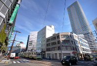 JR広島駅の南東側。高層ビルがそびえるなかを路面電車がゆく=広島市南区で2017年12月3日、山田尚弘撮影