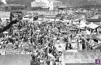 被爆から半年の広島駅前広場に面した松原町下の段に広がる闇市。1946年1月10日にパターソン米陸軍長官が広島を視察した際の警備上の理由から、駅前から南側に移転した。画面右上の広島駅電停にもたくさんの人々が並んでいる。電車は650形電車と思われる。広島駅舎左手の建物には、「JAPAN TRAVEL BUREAU」の看板=広島市猿猴橋町(現広島市南区)の住友銀行東松原支店から北の広島駅方向に向かって撮影1946年2月8日ごろ