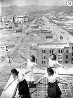 被爆から1年の広島。福屋屋上では花柳舞踊研究生による広島復興小唄の舞踊練習が行われていた。背後は、爆心地相生橋方面。バラックが建ちはじめている。隣の建物は、商工組合中央金庫広島支所。画面奥左から住友銀行広島支店、芸備銀行本店、千代田生命広島支社、広島県産業奨励館(現在の原爆ドーム)、日本赤十字社広島支部、広島県商工経済会。路面を走る電車の姿も見える=広島市胡町(現広島市中区)で1946年7月24日ごろ