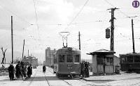 被爆から半年の広島。紙屋町電停に止まっているのは、福島橋手前で被爆した400形413号(1945年11月復旧)で、「己斐」行きの表示が出ている。交差点の中心には戦前・戦中にもあった電車信号所の建物が簡易な形で再建され、有人でポイントの切り替えなどをしている。画面奥に福屋旧館と新館が見える。右端の電車は、401号、402号、417号以外の400形=広島市紙屋町(現広島市中区)の紙屋町交差点から東に向かって撮影1946年2月8日ごろ