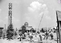 被爆から1年の広島・中島地区の慈仙寺の鼻に建築中の戦災供養礼拝堂。「復興事業に取り掛かる前に犠牲者の供養を」という市民からの強い申し入れを受け、広島市は爆心地への供養塔建設と市内の遺骨収集を計画。左側の広島市戦災死没者供養塔は、1946年5月26日に完成。祈りを捧げる女性と子どもたちが見える。礼拝堂は、8月5日に完成し、6日には戦災死没者1周年追悼会が執行され、数千人の市民が参列した。画面奥左から広島県商工経済会、原爆ドーム、「廣島市戦災死没者供養塔建・・・」と書かれた柱が立っている=広島市中島本町(現広島市中区中島町)で1946年7月24日ごろ