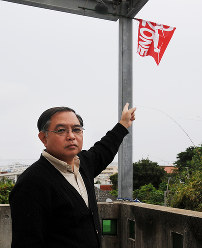 Takehiro Kamiya points at a flag saying 'No Fly Zone' on the second floor balcony of the Midorigaoka day care center in Ginowan, Okinawa Prefecture, on Dec. 19, 2017. (Mainichi)