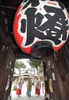 楼門にたまった一年間のすすを払う神職や巫女たち=福岡市博多区の櫛田神社で2017年12月22日午前10時22分、徳野仁子撮影