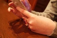 「生きるために、『死にたい』と不安を吐き出してためないようにする」という女子大学生。お守り代わりに、ツイッターで知り合った女性が作った指輪を左中指にはめる=神奈川県で林田七恵撮影