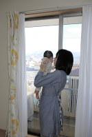 健康科学大学産前産後ケアセンターの宿泊型ケアを利用し、部屋で子どもをあやす女性