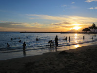 People relax on the shore of a beach in Honolulu at sunset on Nov. 13, 2017. (Mainichi)