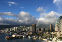 A rainbow fades over buildings near Honolulu Harbor on Nov. 14, 2017. (Mainichi)