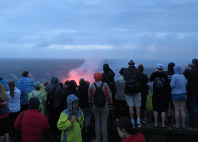 A crowd of people view the Halema'uma'u Crater of the volcano Kilauea outside Jaggar Museum in Hawai'i Volcanoes National Park on Hawaii's Big Island on the evening of Nov. 16, 2017. (Mainichi)