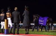 キタサンブラックのお別れセレモニーで、場内を歩くキタサンブラック(右)と見守るオーナーの北島三郎さん(左から3人目)ら=中山競馬場で2017年12月24日午後5時13分、竹内紀臣撮影
