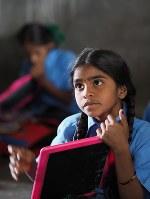 村の教室で読み書きを習う子どもたち。ノート代わりの小さな手持ちの黒板に、文字を書いては消し、を繰り返す