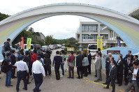 Reporters, local assembly members and others gather outside the Futenma No. 2 Elementary School after hearing that an object believed to be from a U.S. military helicopter had fallen on the school grounds, in Ginowan, Okinawa Prefecture, on Dec. 13, 2017. (Mainichi)