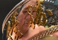 大相撲春場所の表彰式で、造幣局理事長杯に映り込む優勝した稀勢の里=エディオンアリーナ大阪で2017年3月26日、山崎一輝撮影