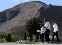熊本地震の本震から1年を迎え、東海大生の脇志朋弥(しほみ)さんが犠牲になったアパート跡を訪れた高橋沙果さん(左端)ら大学の同級生たち。左奥は阿蘇大橋崩落の土砂崩れ跡=熊本県南阿蘇村で2017年4月16日午後0時49分、久保玲撮影