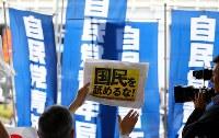 安倍晋三首相も訪れた自民党の街頭演説で抗議の声を上げる人たち(手前)。自民党の旗が目隠しするように、選挙カートとの間に並んだ=東京都千代田区で2017年7月1日午後4時28分、小川昌宏撮影