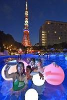 幻想的な雰囲気で写真を撮りながらナイトプールを楽しむ女性たち=東京都港区の東京プリンスホテルで2017年7月20日午後7時半、藤井達也撮影