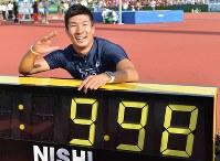 日本学生対校選手権男子100メートル決勝、9秒98で優勝し、時計を前にポーズを取る桐生祥秀=福井運動公園陸上競技場で2017年9月9日、山崎一輝撮影