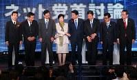 党首討論で議論を終え、カメラマンの求めに応じて率先して握手を促す希望の党の小池百合子代表(左から4人目)と応じようとしない与野党の党首ら=東京都港区で2017年10月7日午後8時45分、小川昌宏撮影