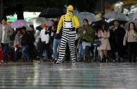 台風22号の影響で雨が降る中、仮装して交差点を渡る人たち=東京都渋谷区で2017年10月29日午後6時11分、小出洋平撮影