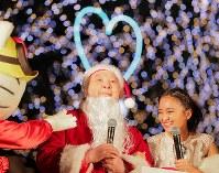 サンタクロース姿で中山競馬場のクリスマスツリー点灯式に登場し、岡田結実さん(右)と笑顔を見せる加藤一二三さん=千葉県船橋市で2017年11月26日、和田大典撮影