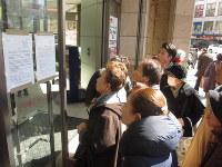 さくら野百貨店仙台店入り口で営業停止を知らせる張り紙を見る買い物客ら=仙台市で2月27日