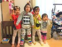 妹たちに囲まれる岸本心咲ちゃん(左から2人目)。装具をつけて立てるようになった=岸本さん提供