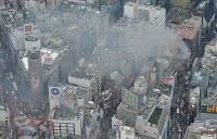 煙を上げて燃える建物(右端付近)。下はJR渋谷駅=東京都渋谷区で2017年12月31日午後2時14分、本社ヘリから宮間俊樹撮影