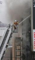煙を上げて燃える雑居ビルの消火活動する消防隊員=東京都渋谷区で2017年12月31日午後2時36分、長谷川直亮撮影