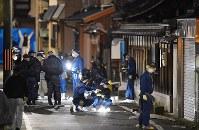 男性2人が刺された現場周辺を調べる捜査員ら=京都市伏見区で2017年12月31日午後5時26分、猪飼健史撮影