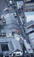住宅街で男性2人が刺された現場を調べる捜査員ら。中央上にとまっているのは、被害者の男性が所有しているとみられるワゴン車=京都市伏見区で2017年12月31日午後4時42分、本社ヘリから三村政司撮影
