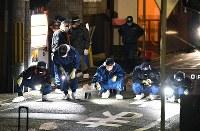 路上に照明をあて、男性2人が刺された事件現場周辺を調べる捜査員ら=京都市伏見区で2017年12月31日午後6時5分、猪飼健史撮影