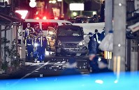 住宅街で男性2人が刺された現場を調べる捜査員ら。被害者の男性が所有しているとみられるワゴン車は、前部のバンパーが破損している=京都市伏見区で2017年12月31日午後7時44分、猪飼健史撮影(画像の一部を加工しています)