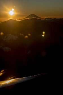 ANAの初日の出フライトで窓から見えた富士山越しの初日の出=長野県駒ケ根市上空で2018年1月1日午前、米田堅持撮影