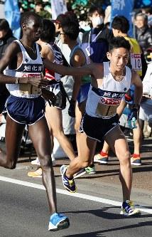 2区のキプヤティチ(左)から1位でたすきを受け取る旭化成の市田孝(右)=前橋市で2018年1月1日、小川昌宏撮影