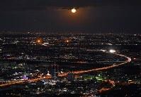 帰省先などからのUターンラッシュで、満月が昇る東京方面(奥)への車が渋滞する東名高速道路・厚木IC付近=神奈川県厚木市で2018年1月2日午後5時19分、本社ヘリから手塚耕一郎撮影