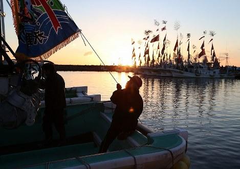 震災後初めて請戸漁港で行われる出初め式の準備で大漁旗を漁船に掲げる漁師=福島県浪江町で2018年1月2日午前7時2分、小出洋平撮影