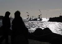 震災後初めて請戸漁港で行われた出初め式で、大漁旗を掲げて沖に出る漁船=福島県浪江町で2018年1月2日午前8時44分、小出洋平撮影