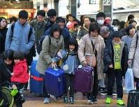 Uターンラッシュがピークを迎え、大きな荷物を手に、東北・信越方面から到着した新幹線を降りた乗客たち=JR東京駅で2018年1月3日午後3時半、手塚耕一郎撮影