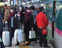 Uターンラッシュがピークを迎え、大きな荷物を手に、東北方面から到着した新幹線を降りる乗客たち=JR東京駅で2018年1月3日午後4時27分、手塚耕一郎撮影