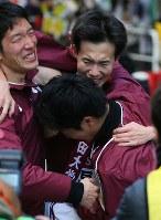 3位でフィニッシュしチームメートに抱えられる早稲田大アンカーの谷口耕一郎(中央上)=東京都千代田区で2018年1月3日、宮武祐希撮影