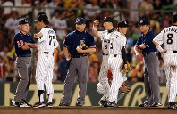 In this Sept. 6, 2003 file photo, Hanshin Tigers manager Senichi Hoshino, along with team members, protests a home-run ruling during a game against the Yokohama BayStars at Koshien Stadium. (Mainichi)