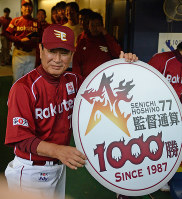 In this May 11, 2012 file photo, Rakuten Eagles manager Senichi Hoshino shows off a sign celebrating his 1,000th win as a manager at Kyocera Dome Osaka. (Mainichi)