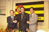野崎勝義球団社長(左)、星野仙一監督(右)と握手する田淵幸一氏=2001年12月、望月亮一撮影