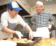焼き上がったパンを前に笑顔をみせる山田和夫さん(右)と 元路上生活者の男性=東京都豊島区で