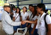 中米エルサルバドル・アカフトラで行った同国内戦の被害者との証言交流会の後、学生と握手する宮田隆さん。長崎での被爆者=2013年9月撮影、ピースボート提供