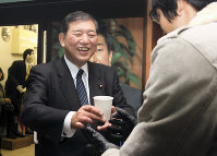 Former Liberal Democratic Party Secretary-General Shigeru Ishiba smiles as he hands hot tea to passersby in front of his office in Tottori, on Jan. 1, 2018. (Mainichi)