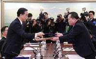 南北閣僚級会談終了後、採択された共同報道文を交換する韓国の趙明均統一相(左)と北朝鮮の祖国平和統一委員会の李善権委員長=板門店で9日、ロイター