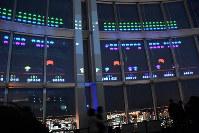 六本木の夜景を見下ろす窓に投影されたインベーダーを倒す「SPACE INVADERS GIGAMAX」=2018年1月11日、村田由紀子撮影