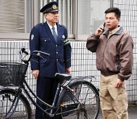 携帯電話をつかって110番通報をするベトナム人技能実習生=松山市北土居3の松山南署で、木島諒子撮影