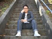 階段に腰掛けて自然体のポーズ。「何事も面倒くさがらずに腰を上げると、面白いことはたくさんある」=東京都千代田区で、中村藍撮影